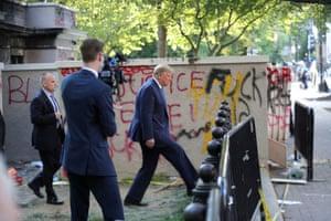 Donald Trump walks past graffiti
