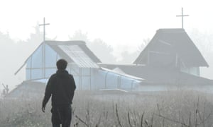 A man walks past a makeshift church in the migrant camp in Calais, France.