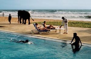 Tourists lounge poolside as elephant passes, Bentota, Sri Lanka, 1995