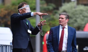 Keir Starmer walks past an employee as he leaves the Garden Museum, south London, after holding a press conference.