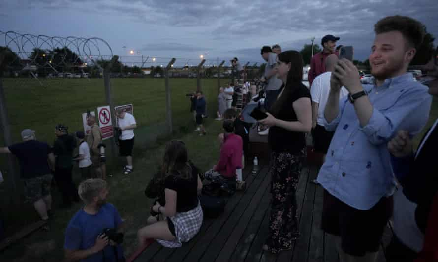 People wait to see Air Force One, carrying Joe Biden and first lady Jill Biden, take off from RAF Mildenhall in Suffolk last night en route for Cornwall.