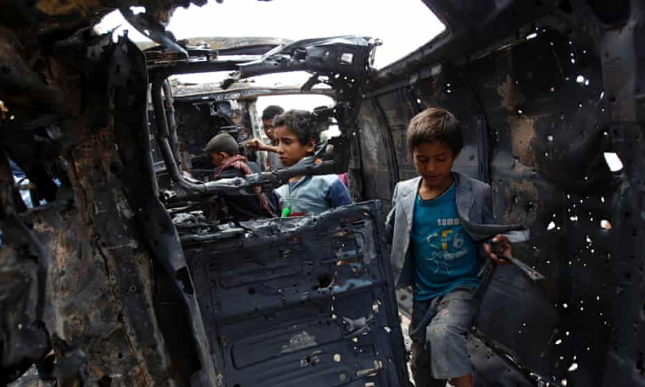 Yemeni children inspect a charred vehicle after two improvised explosive devices went off in the capital, Sana'a.