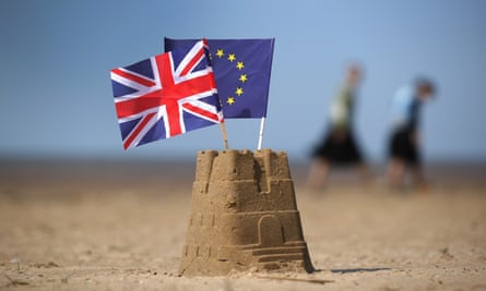 A sandcastle with EU and UK flags
