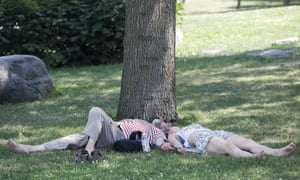 Two people feel the heat in a park in Montreal on 5 July.