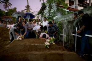 Mourners at the burial of three victims from the same family, who died at the Easter Sunday bomb blast at St Sebastian Church in Negombo, Sri Lanka.
