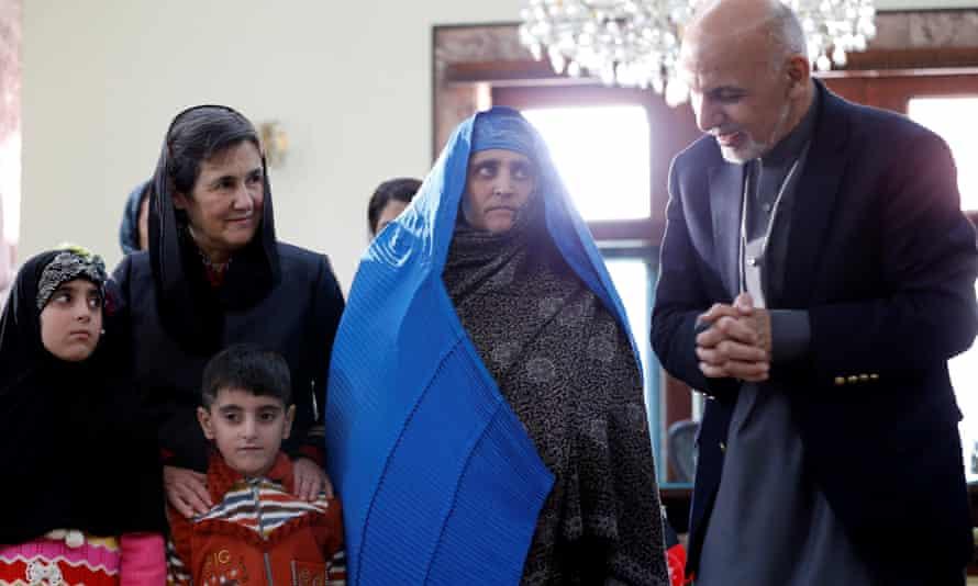 Afghanistan's president Ashraf Ghani speaks to Sharbat Gula, in blue, in Kabul on Wednesday.