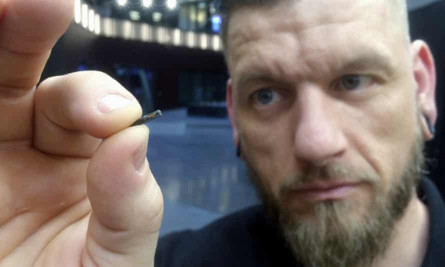 Jowan Osterlund from Biohax Sweden holds a small microchip implant, similar to those implanted into volunteers at the Australian Centre for the Moving Image