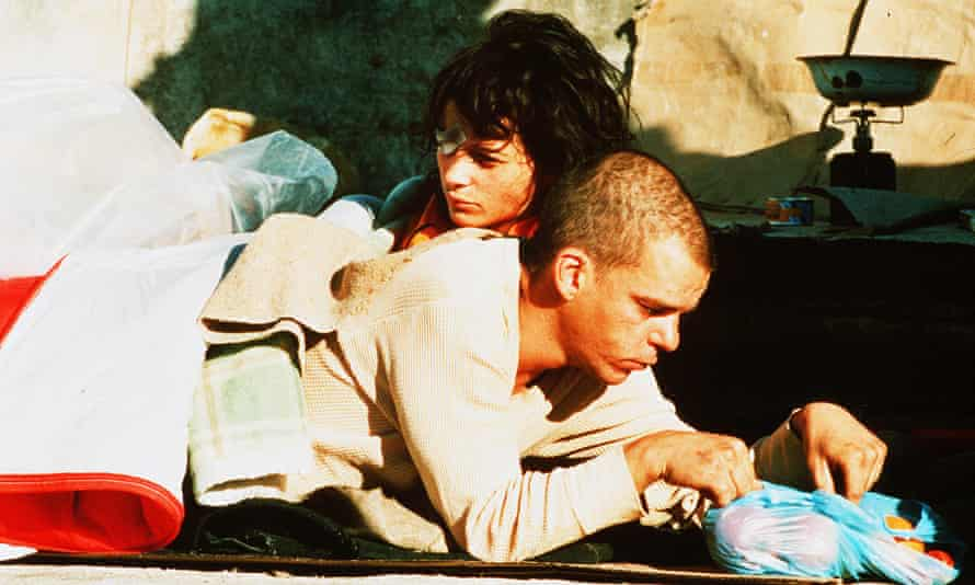 Lying alongside and holding Denis Lavant, who is looking down
