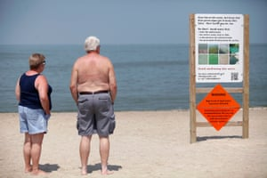 Signs on the Lake Erie beach warn about the algae in August 2014.