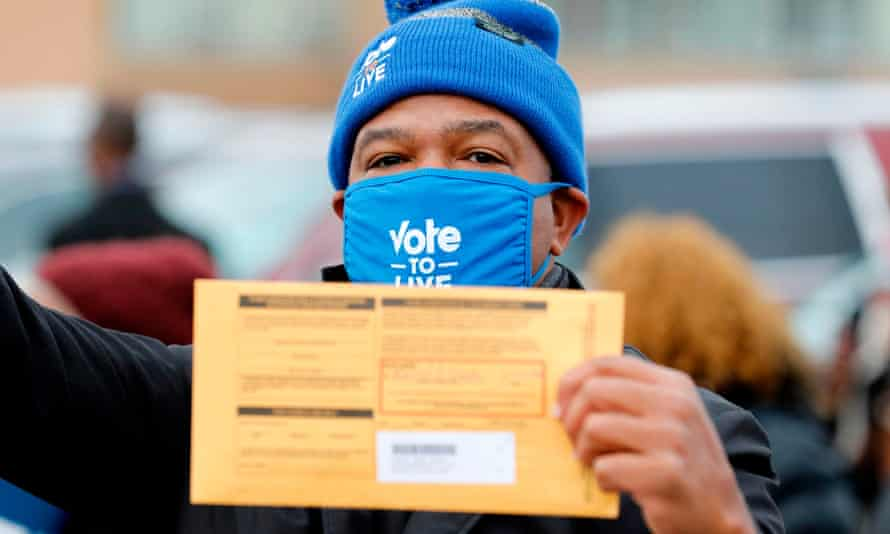 A voter holds his sealed ballot on 25 October 2020 in Detroit, Michigan.