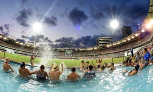 Spectators watch the action from a swimming pool on the boundary of the Gabba on day one of the first Test match between Australia and Pakistan in Brisbane.