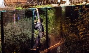 A migrant climbs a security fence by the Eurotunnel terminal in Coquelles near Calais