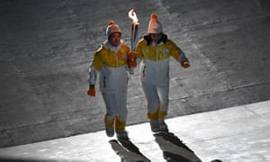 Torch bearers carry the Olympic flame into the Pyeongchang Olympic Stadium
