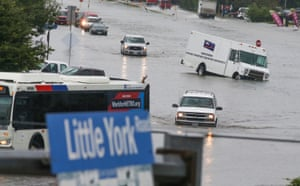 Cars are flooded as people walk though the street of Little York on 19 September 2019 in Houston, Texas.