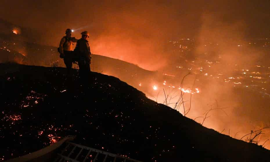 Firefighters look out over a burning hillside as they fight the Blue Ridge Fire in Yorba Linda, California, 2020.