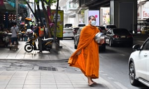 A monk wears a protective face mask along the road side in Bangkok.