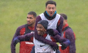 Ashley Young, bottom, enjoys a laugh with Jesse Lingard during an England training session.