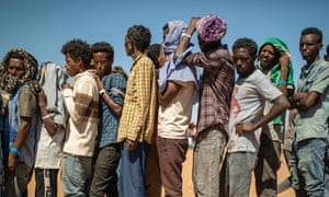 Refugees queue for food distribution in at the Um Raquba settlement.