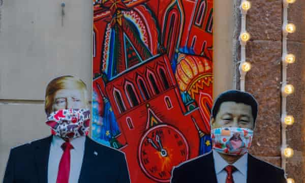 Cardboard figures of Chinese president Xi Jinping and US President Donald Trump wearing face masks stand near souvenirs shop in Moscow, Russia, 24 March 2020.