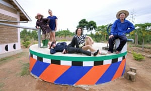 Graphic artist Camille Walala and her collaborator Julia Jomaa sit alongside residents of Ukerewe on a brightly coloured water towe