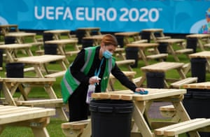 Justine Ralston cleans tables as finishing preparations are made to the UEFA EURO 2020 Fan Zone at Glasgow Green.