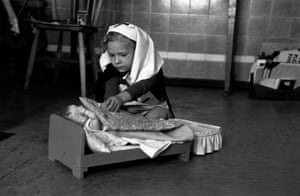 Fancy Dress, 1954. A child in a nurse's costume plays with a doll at the Guy's hospital nursery for sick children, in London