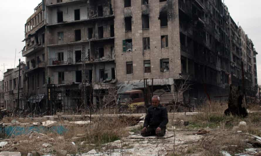 A man praying near the Umayyad mosque in the ruins of Aleppo