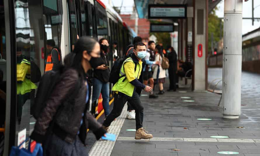 Commuters wearing masks disembark from the light rail at Central station in Sydney, Australia