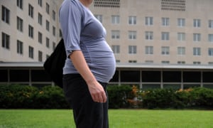 A pregnant woman walks past a government building in Washington DC