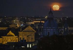 A full moon rises over the Rome's skyline