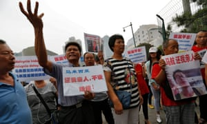 Chinese relatives of passengers of missing flight MH370 protest outside the Malaysian embassy in Beijing.