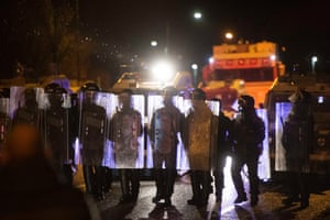 Police hold riot shields during clashes with nationalist youths