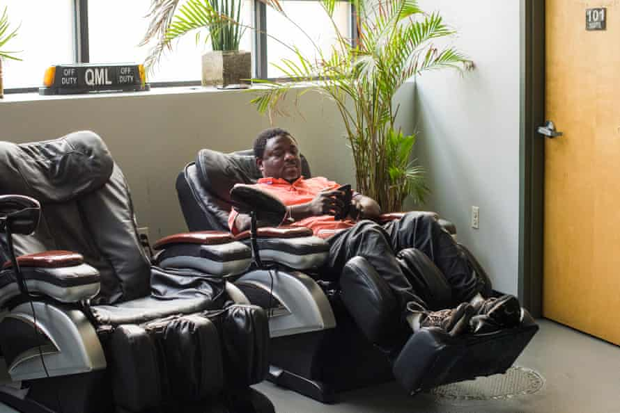 Ignimora Atarouanourou, 39, from Togo, followed his father into the taxi business. He sits in a massage chair in the taxi garage during a break.