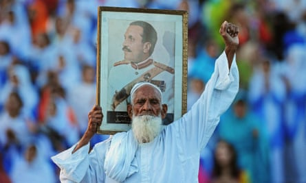 a man holds a picture General Zia ul-Haq, during a ceremony at the Wagha border, the only road crossing between India and Pakistan.