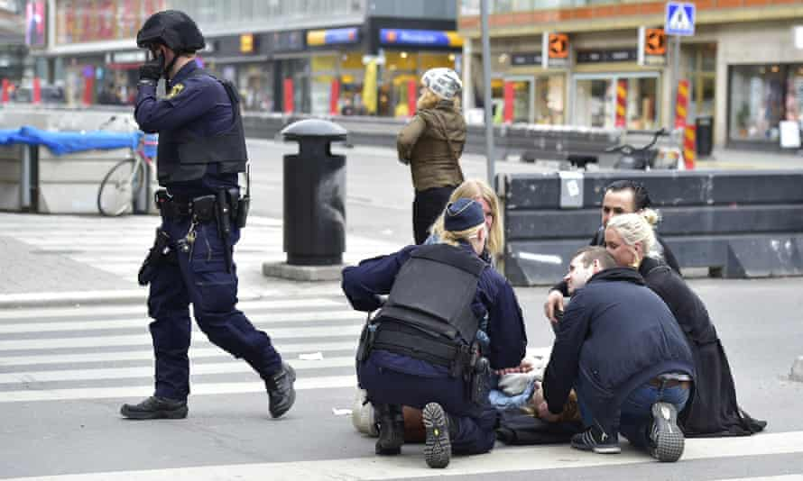 Police assist people on the streets of Stockholm.