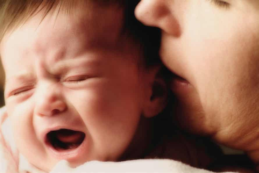 Mother holding crying new born