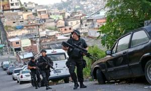 Police officers patrol the Alemão favela, Rio de Janeiro, in 2014.