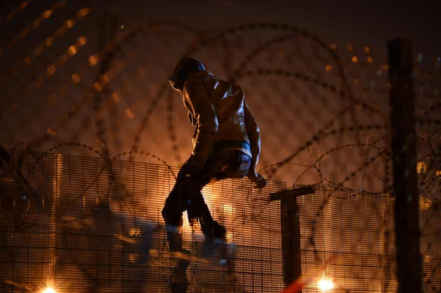 A migrant camped attempts to climb a security fence near refugee camp of Calais