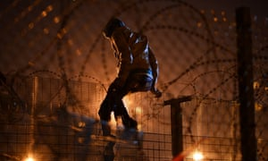 'It is an act of welcome' … a refugee climbs a security fence in Calais, France.