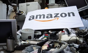 A placard with Amazon's logo atop lots of trashed appliances