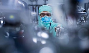 A lab technician, wearing personal protective equipment, prepares stainless steel tanks for manufacturing vaccines
