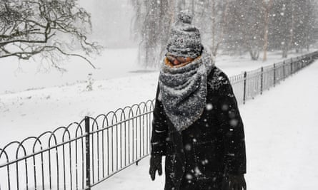 A person walks through heavy snow in St James's Park in central London