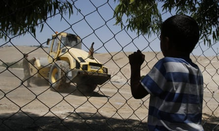 A child in Khan al-Ahmar gazes through a fence at a bulldozer