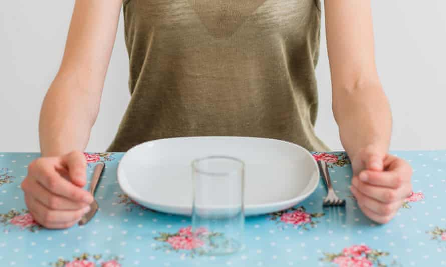 woman in front of an empty plate.