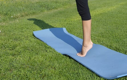 A woman standing on tip toe on a yoga matt in a field.