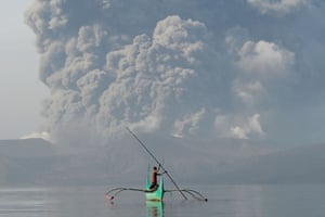 A boy guides an outrigger canoe in the lake around Taal volcano