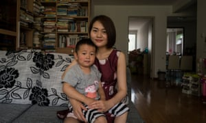 Li Wenzu, 31, wife of imprisoned lawyer Wang Quanzhang poses for a portrait with their son Wang Guangwei, 3.