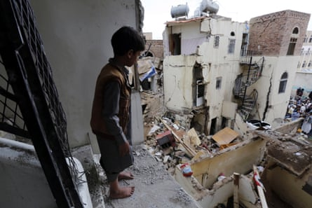 A boy looks over destroyed houses the day after a Saudi-led airstrike in Sanaa