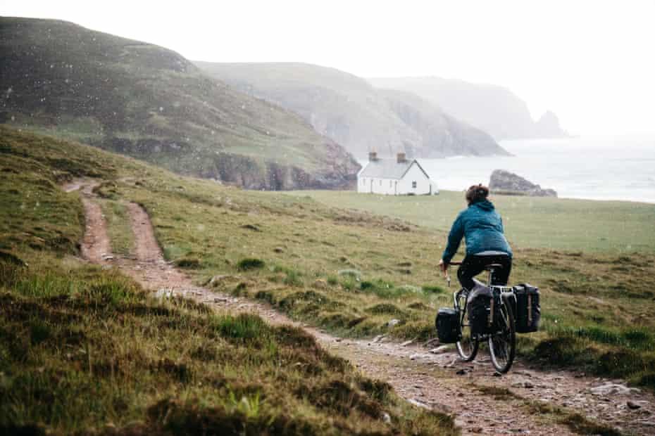 Cyclist approaches Kearvaig Bay, Scotland.