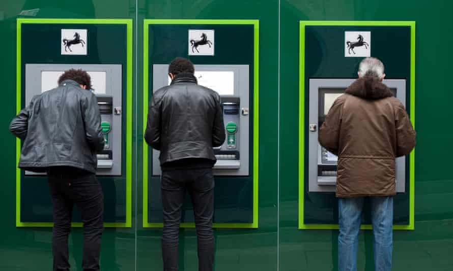 Customers use an ATM outside of a branch of Lloyds Bank in London